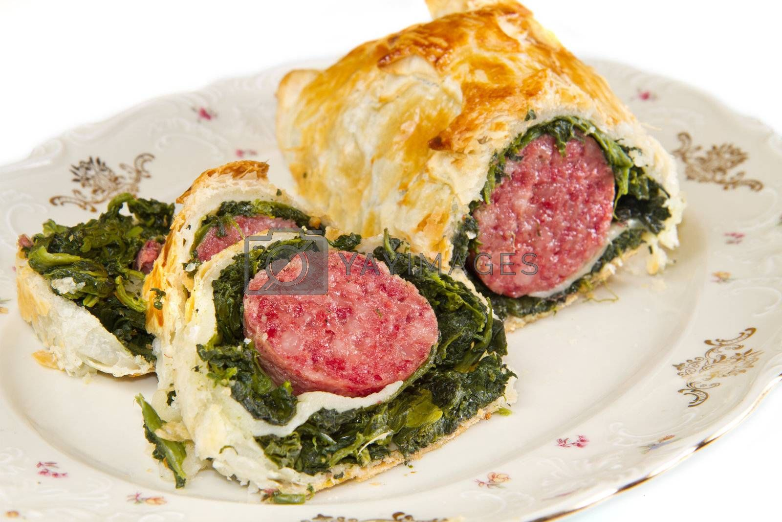 italian cotechino in crust with spinach on dish