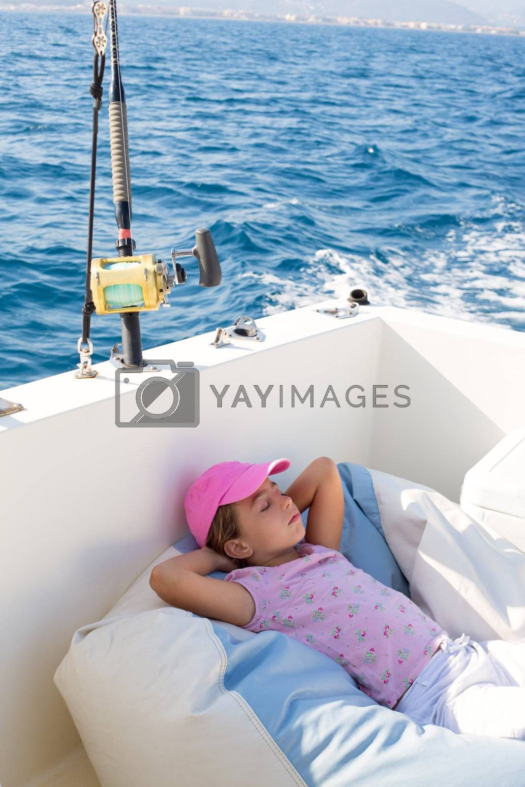 child girl sailing relaxed on boat deck enjoying a nap in blue sea
