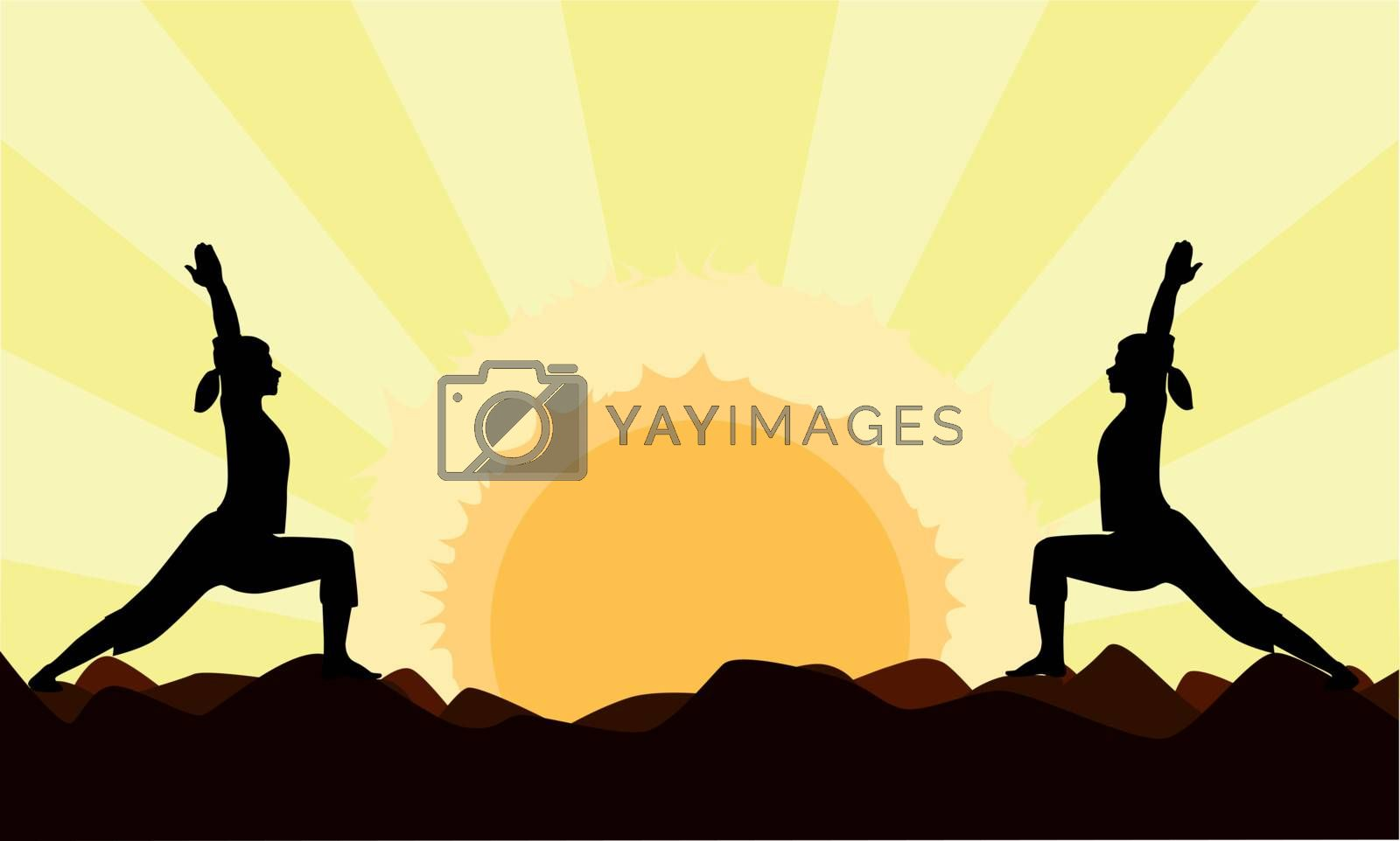 Two women practicing the yoga tree pose to the setting or rising sun with space for additional text.