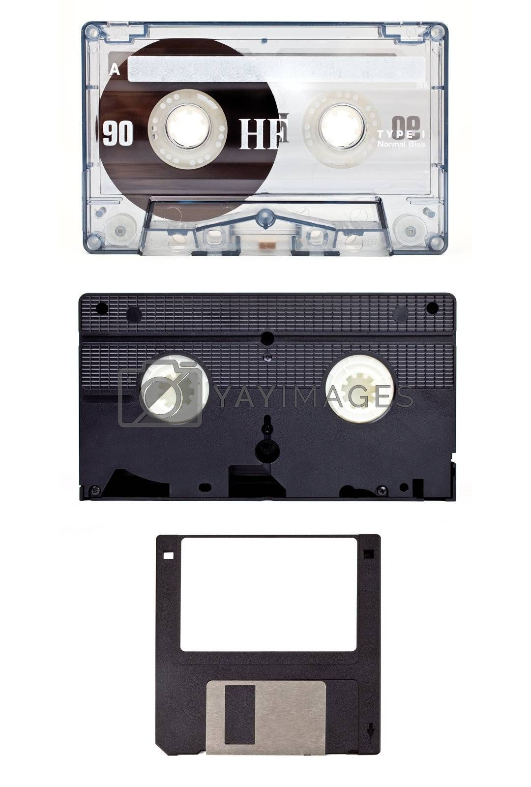 Old technology devices - Audio Cassette Tape, Video Tape and a Floppy Disc.
