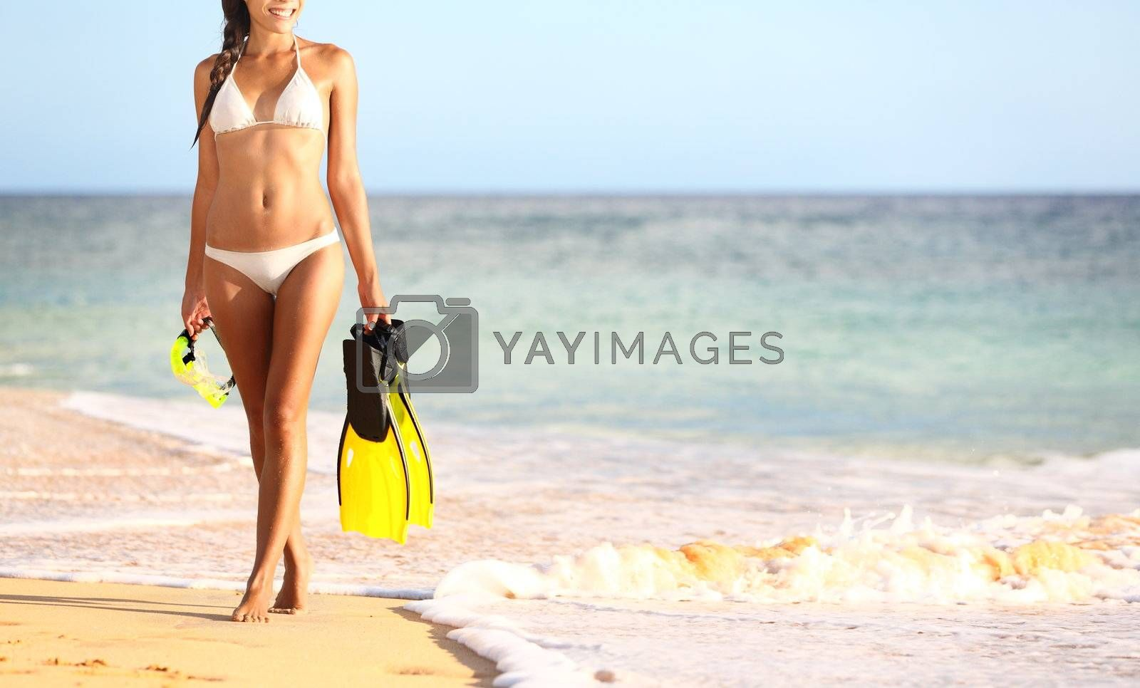 Beach summer travel holidays vacation concept with woman in bikini walking on sunny beach holding snorkeling equipment, fins and mask. Photo from Makena Beach, Maui, Hawaii.
