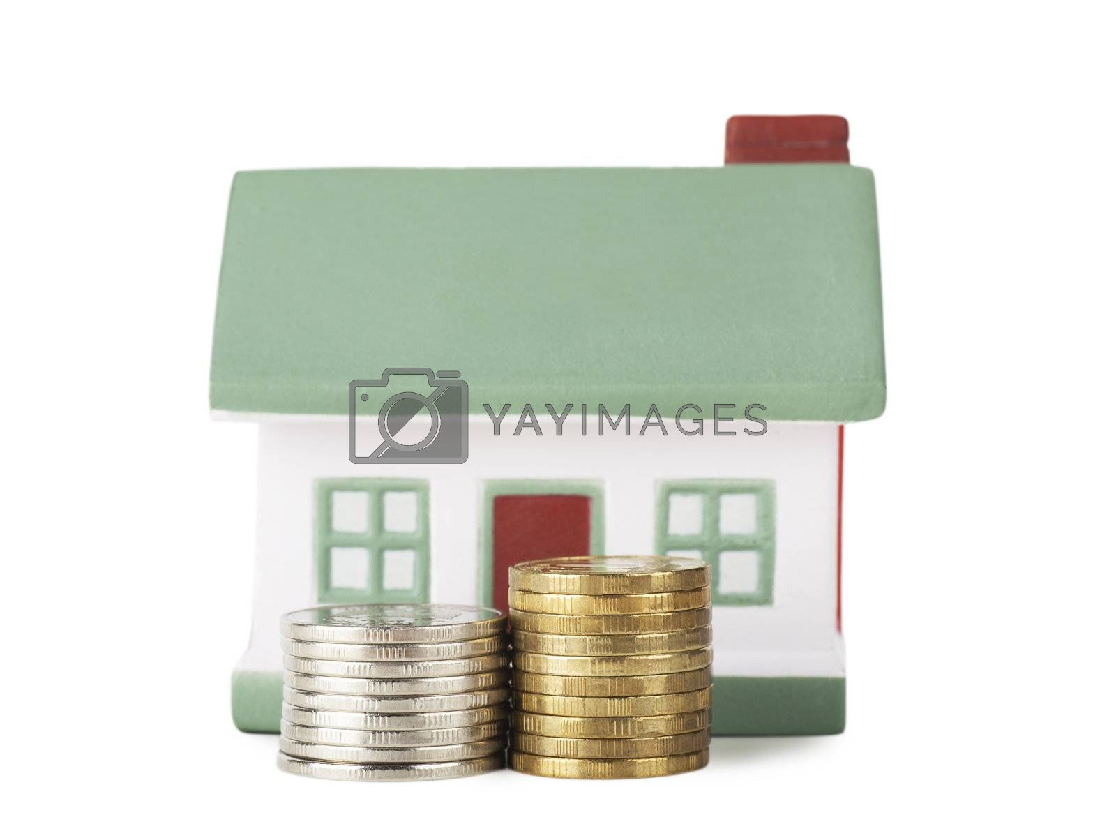 Little house toy and two stacks of coins isolated over white background
