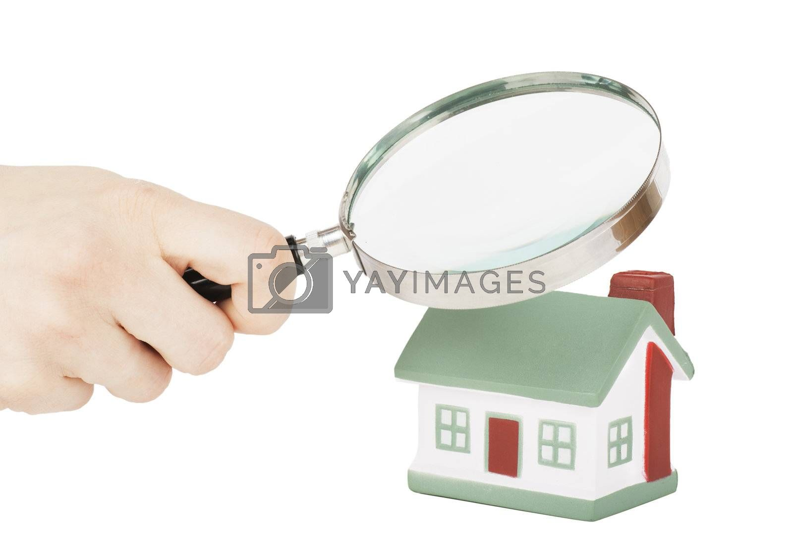 Toy of house and hand with magnifying glass isolated over white background