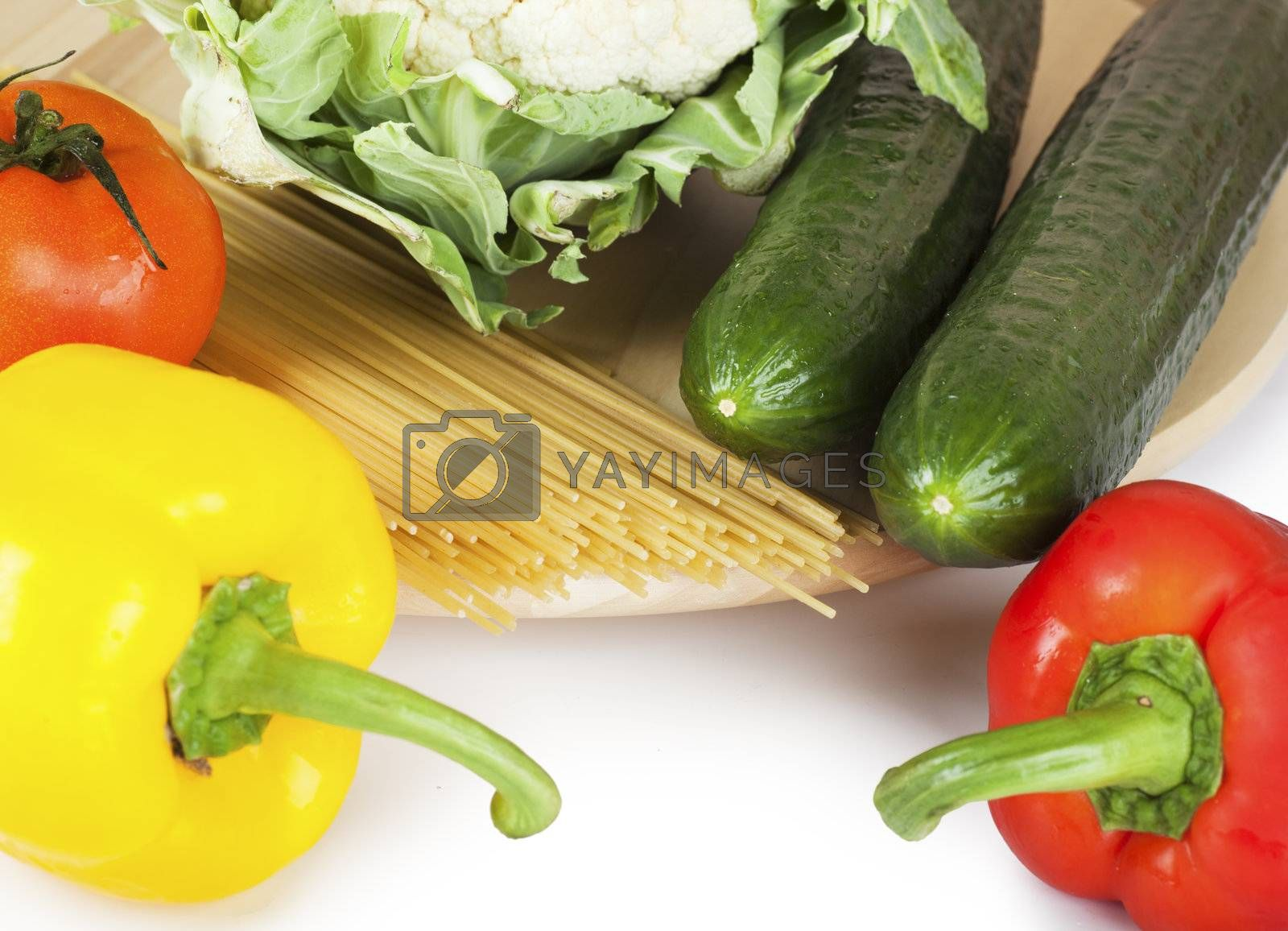 Vegetables (pepper, tomato, caulflower, cucumber) and spaghetti over white background