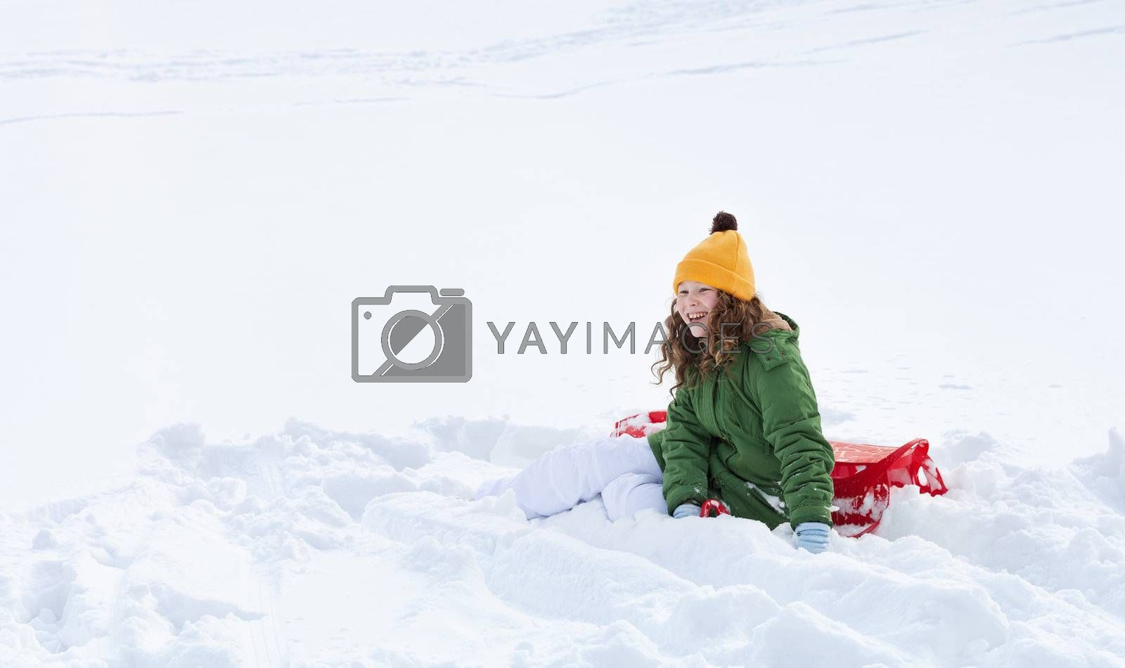 Smiling teenager girl with red plastic sledge sitting in snow