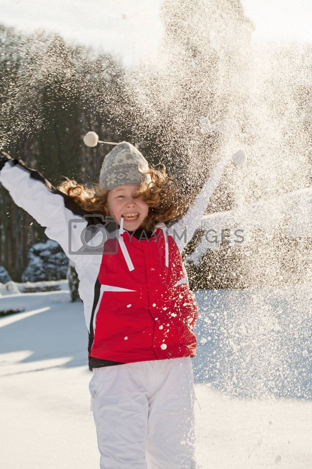 Happy teenager girl in a winter park throwing snow up - motion blur on girl's face