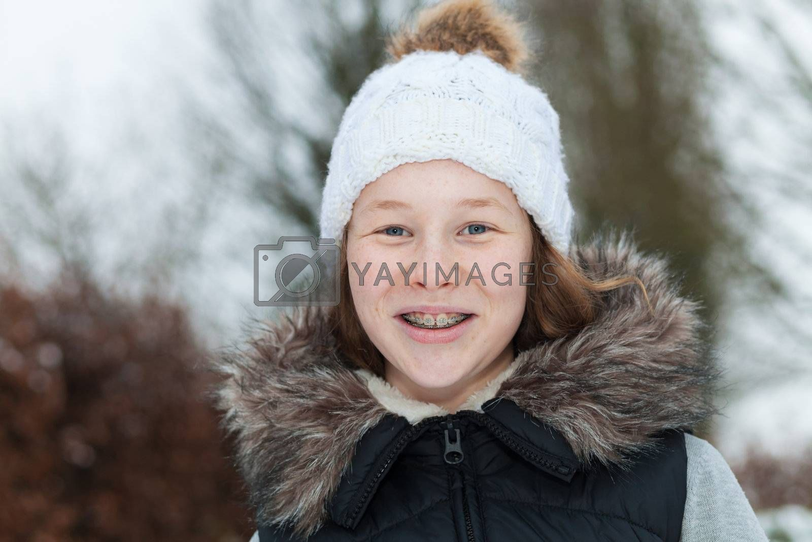 Outdoor portrait of a smiling teenager girl in winter clothing