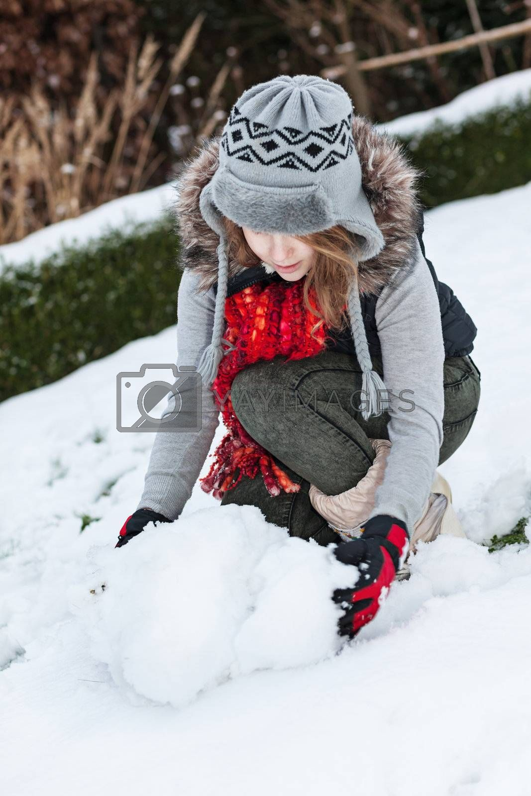 Teenager girl making snowman in snowy back yard