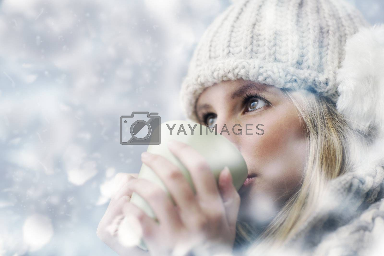 Young woman wearing winter clothes having a hot drink