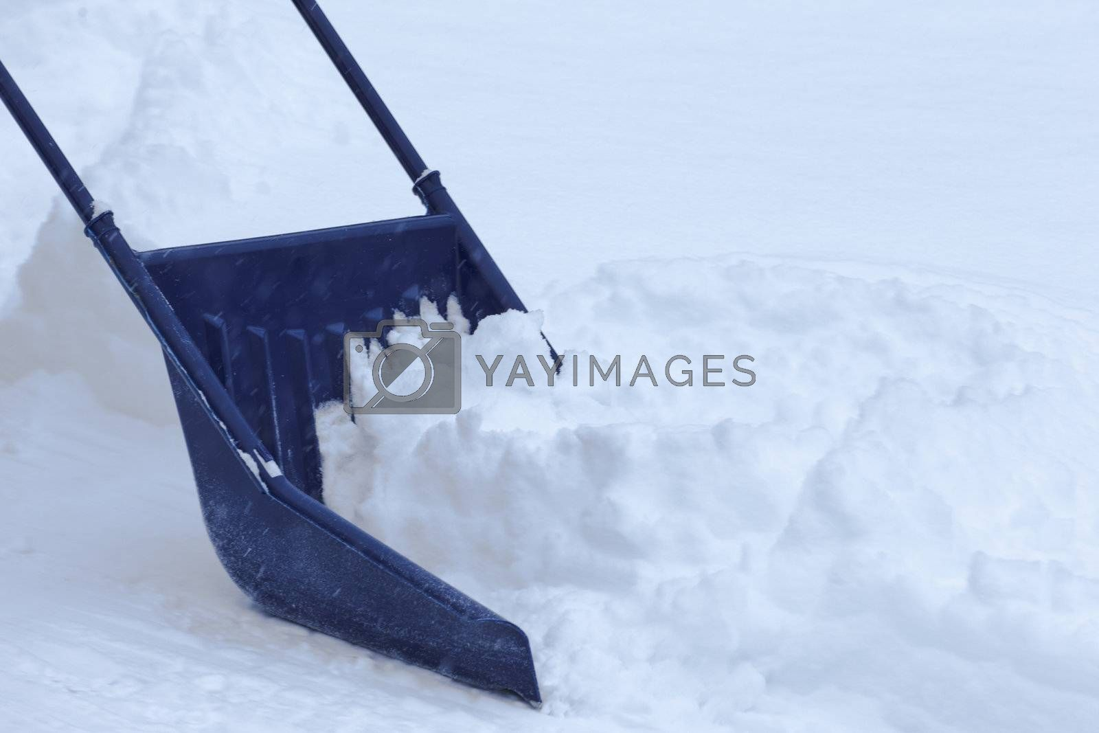 Manual snow removal from driveway using a snow scoop after blizzard