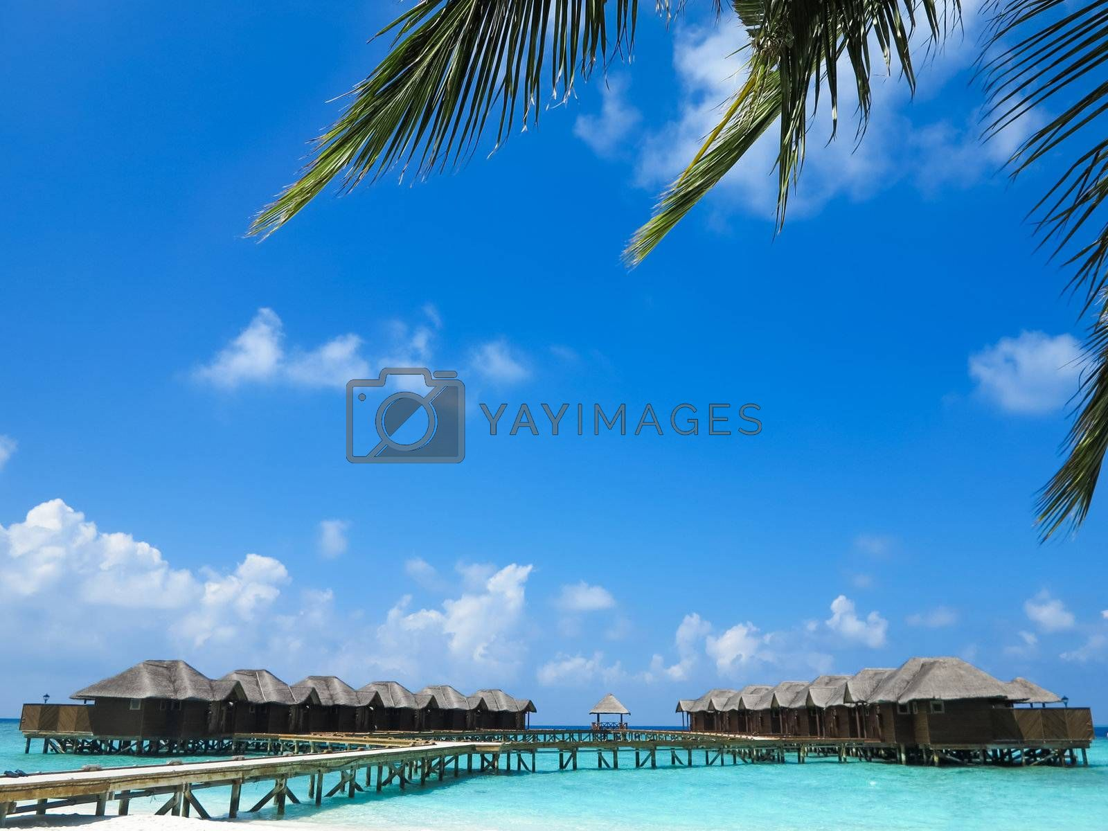Scenic beauty of ocean cottages, clear blue sky with clouds.