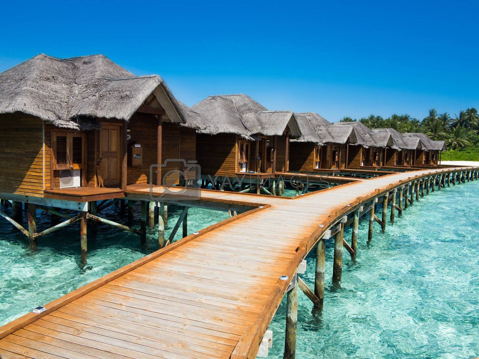 Timber laid walk path leading to cottages over water, maldives.