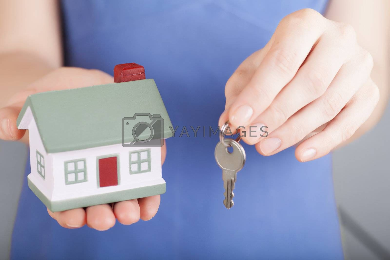 Little house toy and a key in woman's hands