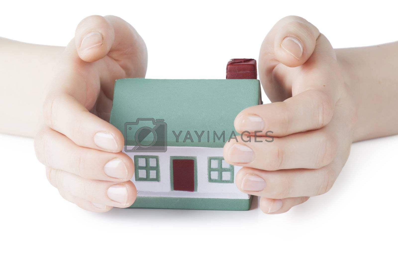 Little house toy covered by hands over white background