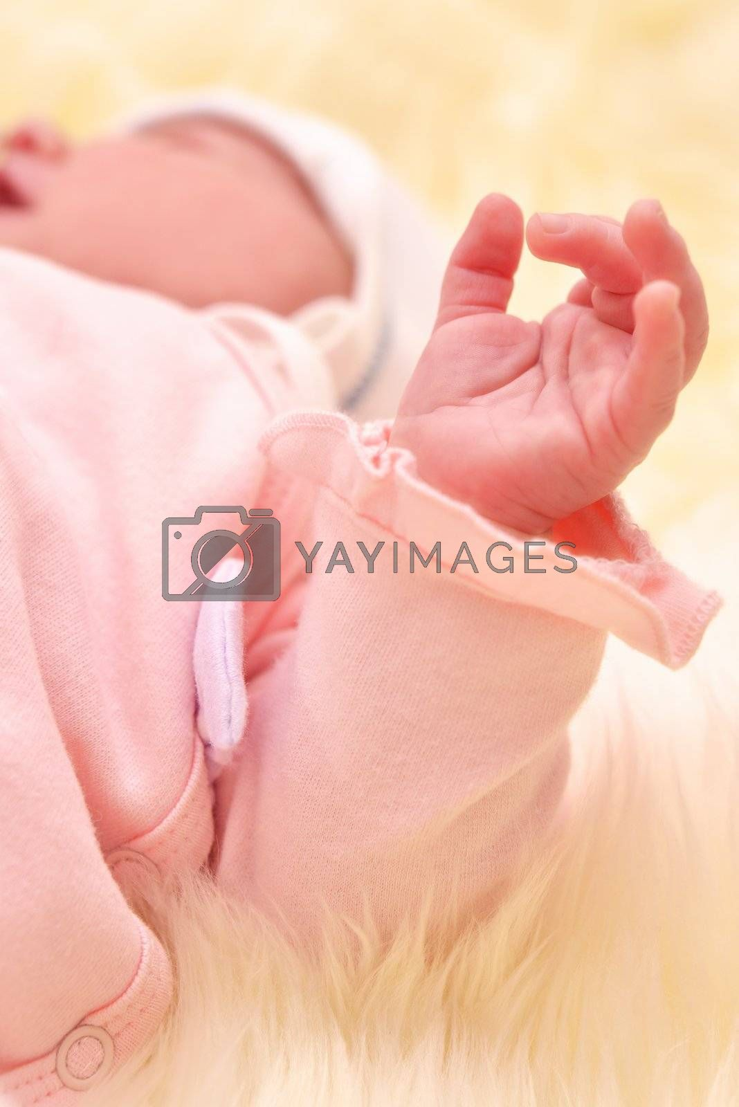 Sleeping baby arm in a pink dress with a blurred background.