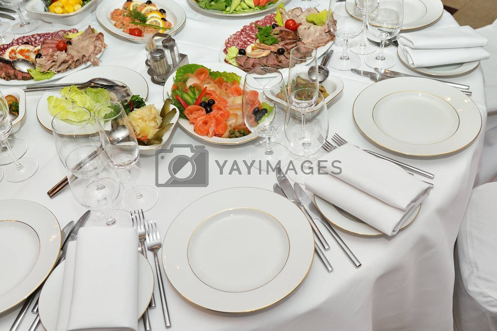 Served table with appetizers, dishes and glasses.