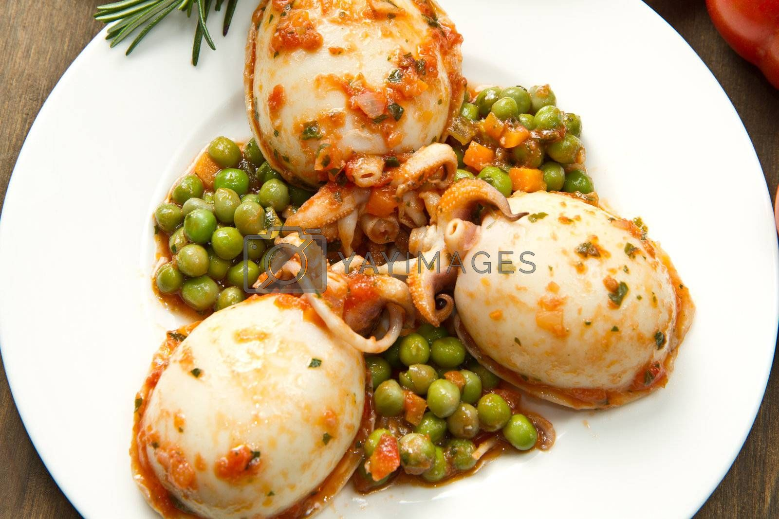 a white bowl with cuttlefish with peas and fresh tomatoes, lemon and oil