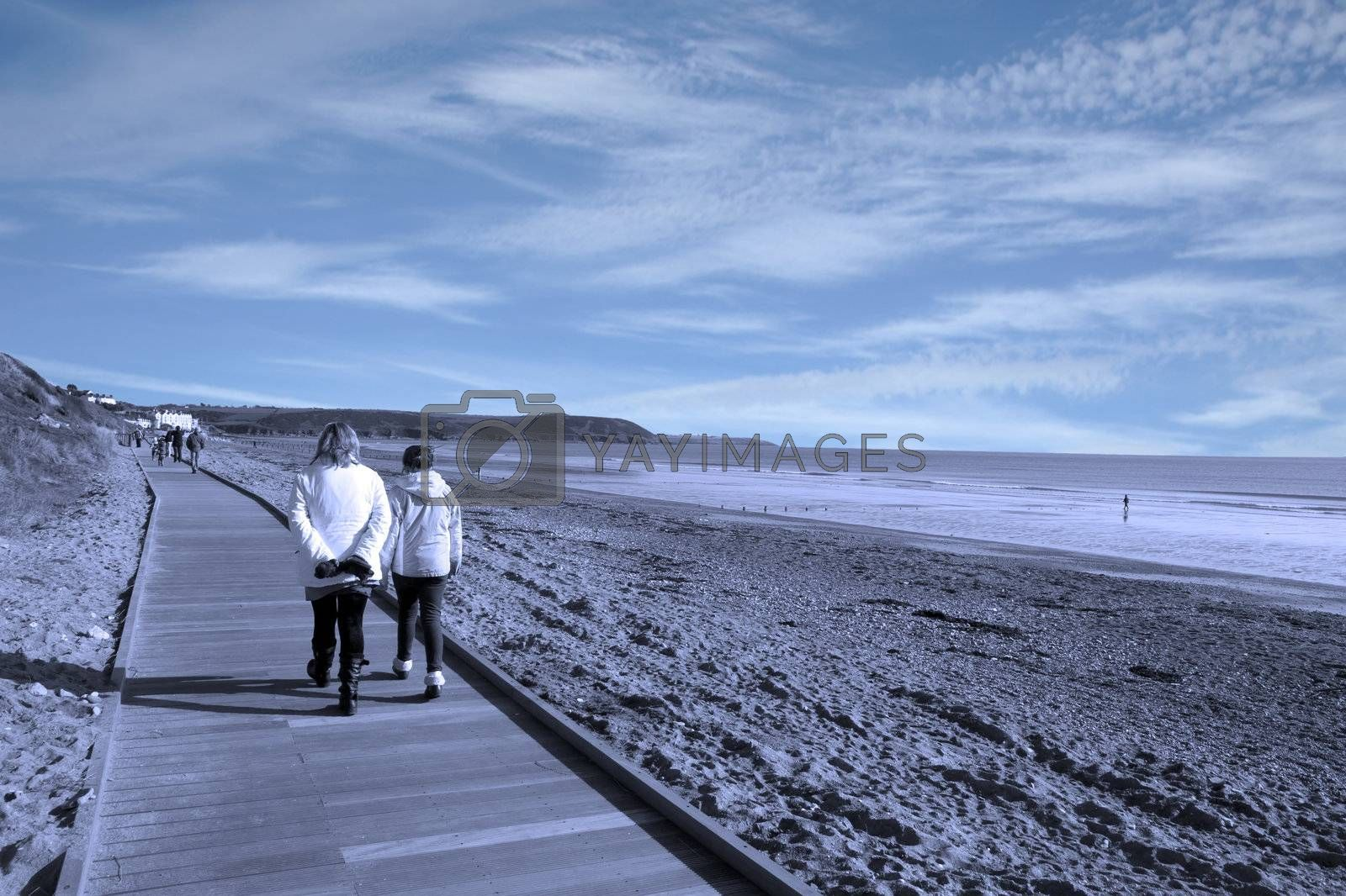 mother and daughter strolling along the beach boardwalk in Youghal county Cork Ireland