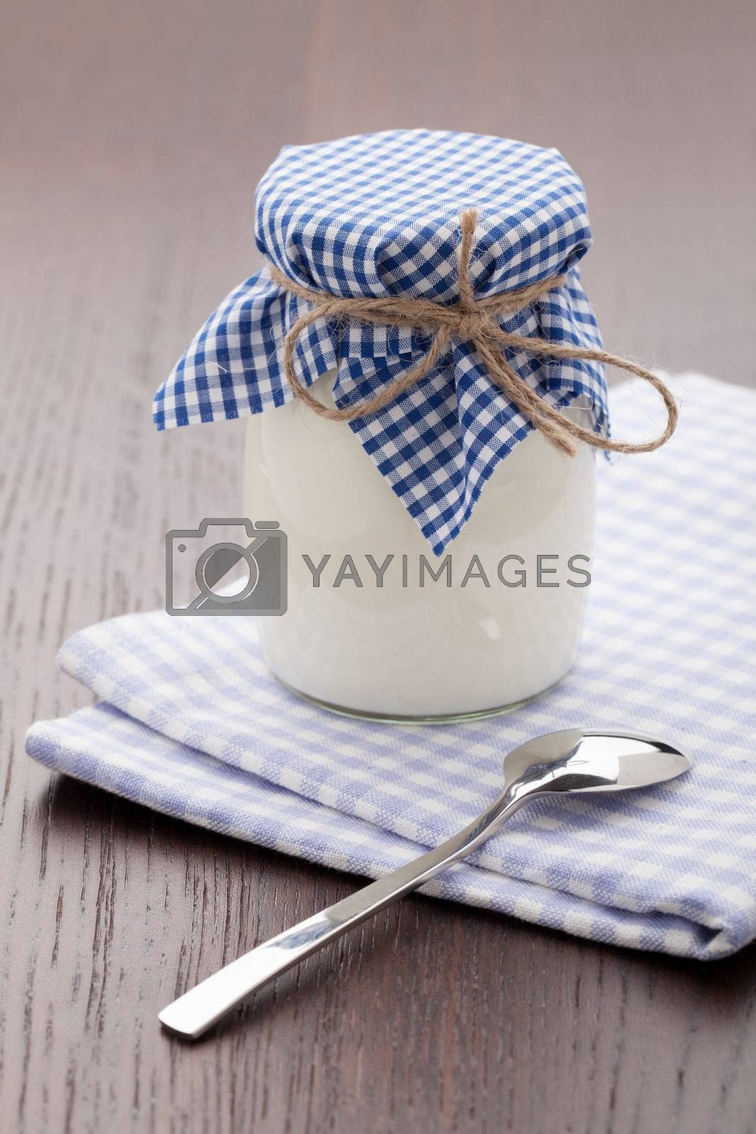 Homemade milk yogurt in glass pot and metal spoon served on linen napkin wooden table