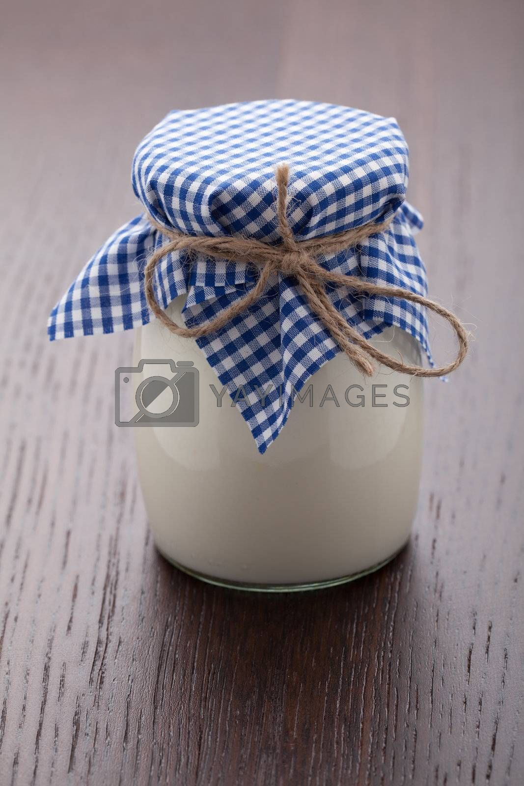 Homemade milk yogurt in glass pot served with linen napkin on wooden table