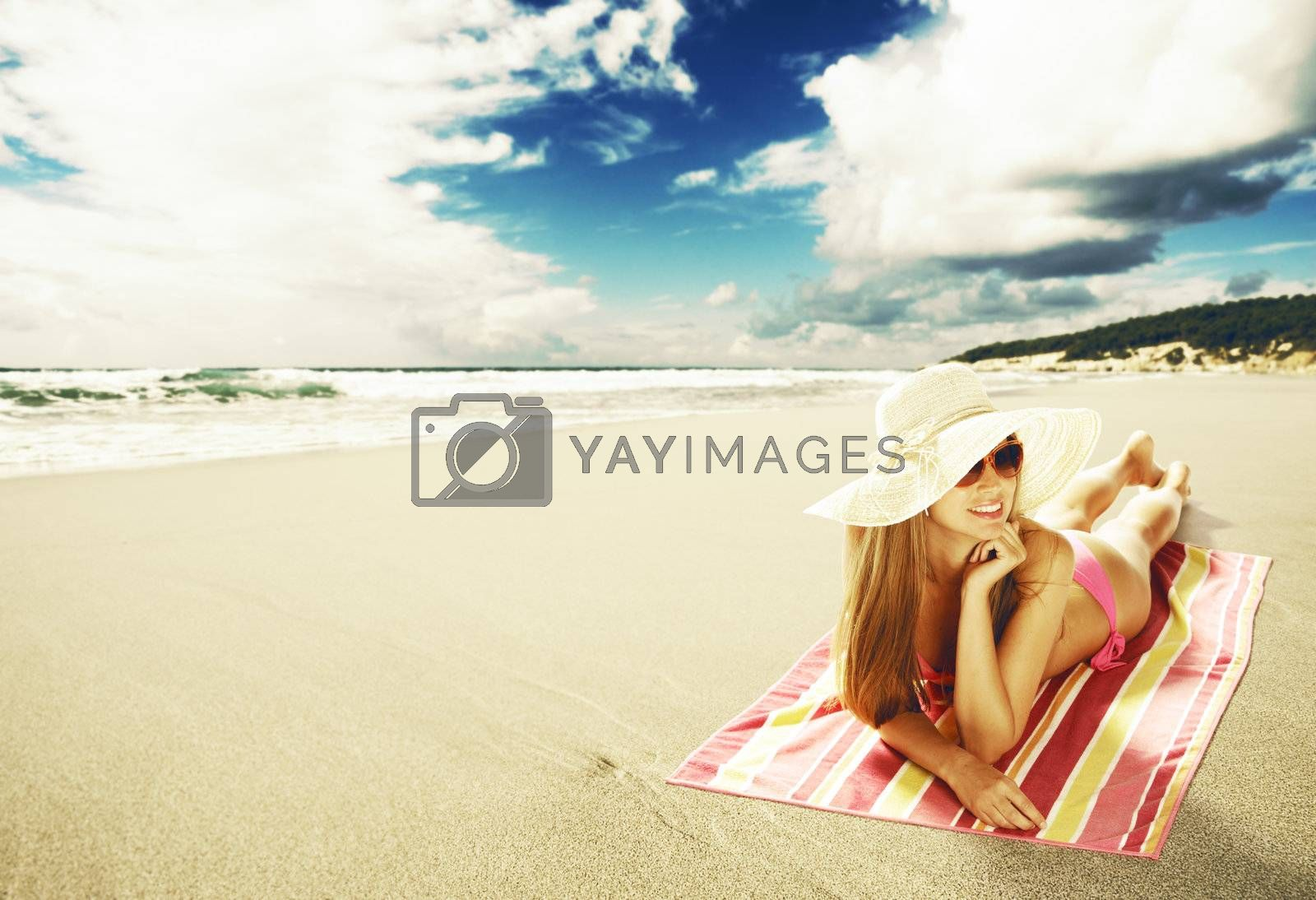 Sexy young woman lying down on the beach