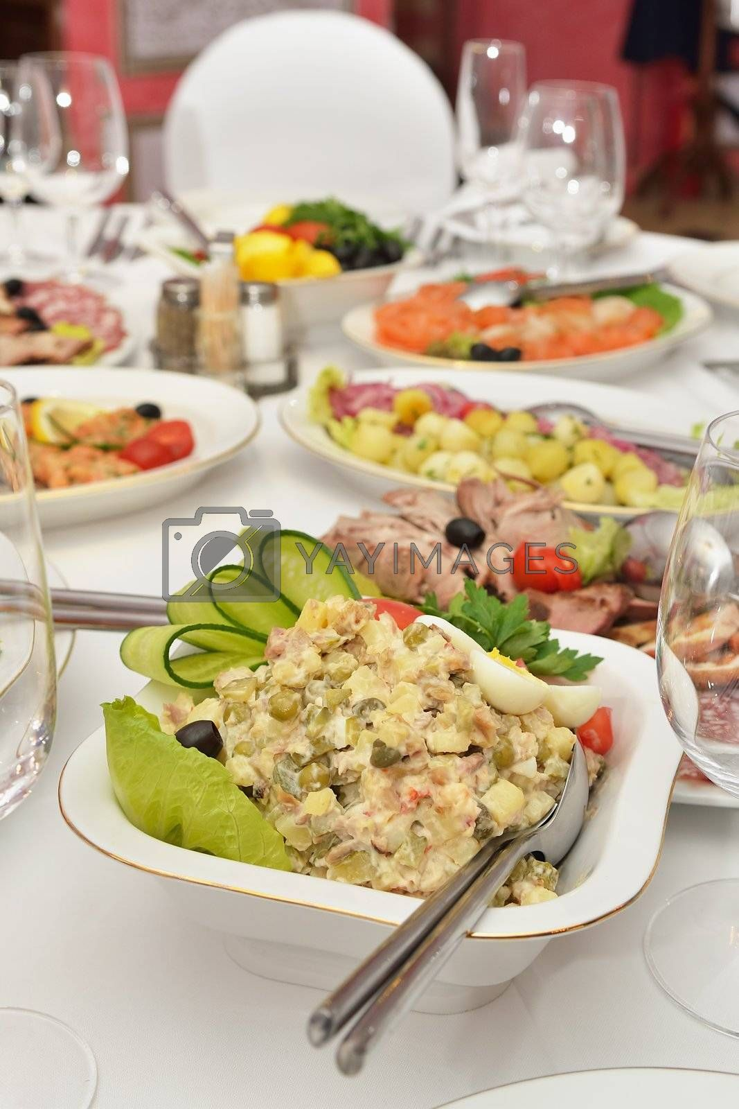 Salad on the served table. Snacks, wine glasses and restaurant serving.