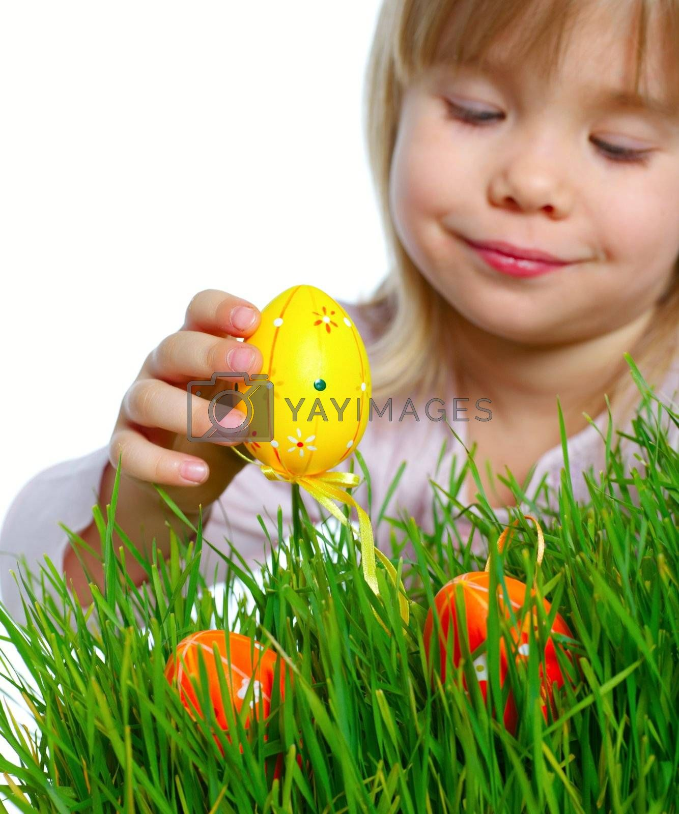 Adorable little girl collecting Easter eggs in her basket. Focus on the egg. Isolated white backround