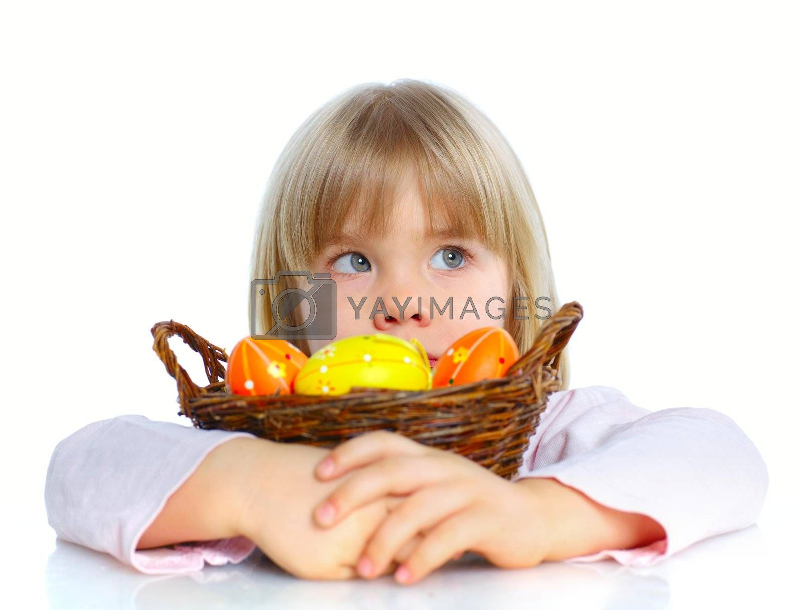 Adorable little girl collecting Easter eggs in her basket