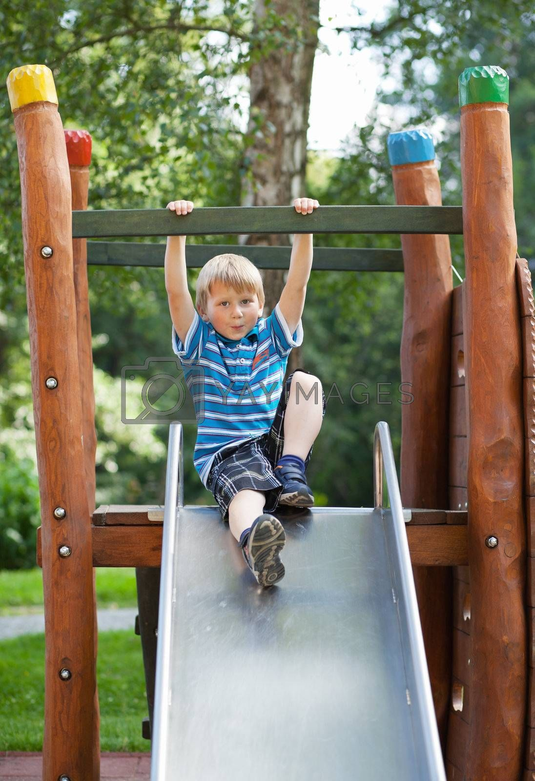 Little blond boy on an outdoor playground
