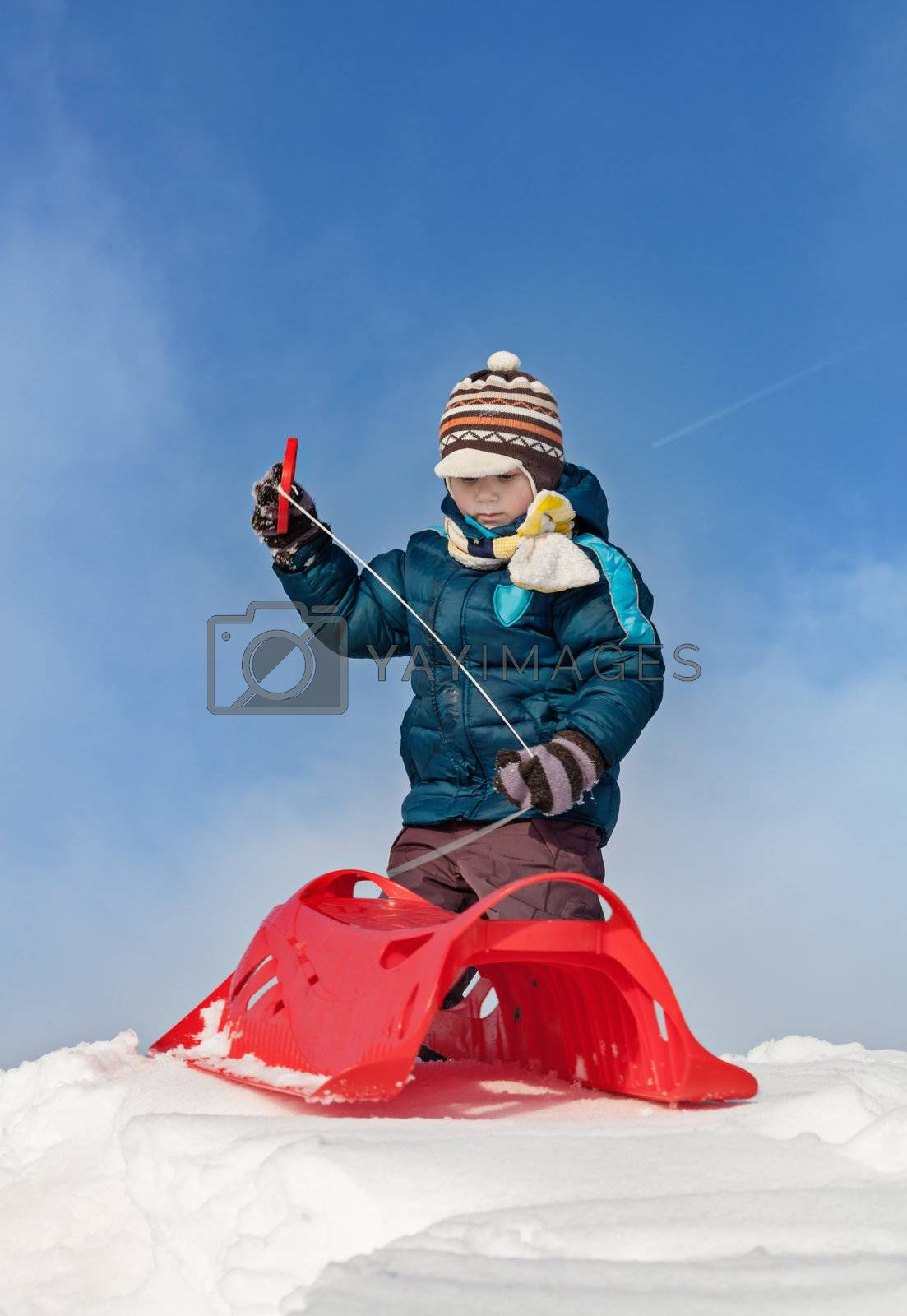 Boy preparing for a ride with red plastic sleigh on a snowy hill in sunny winter day