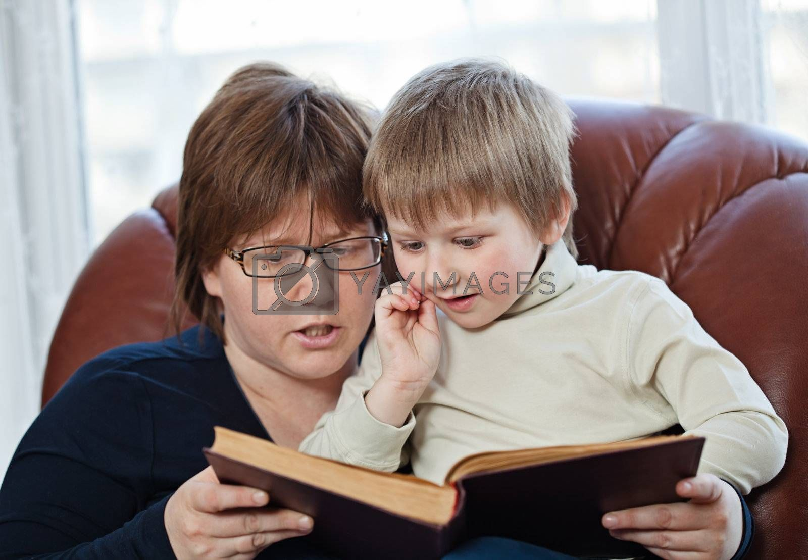 Mother and her little child reading a book together