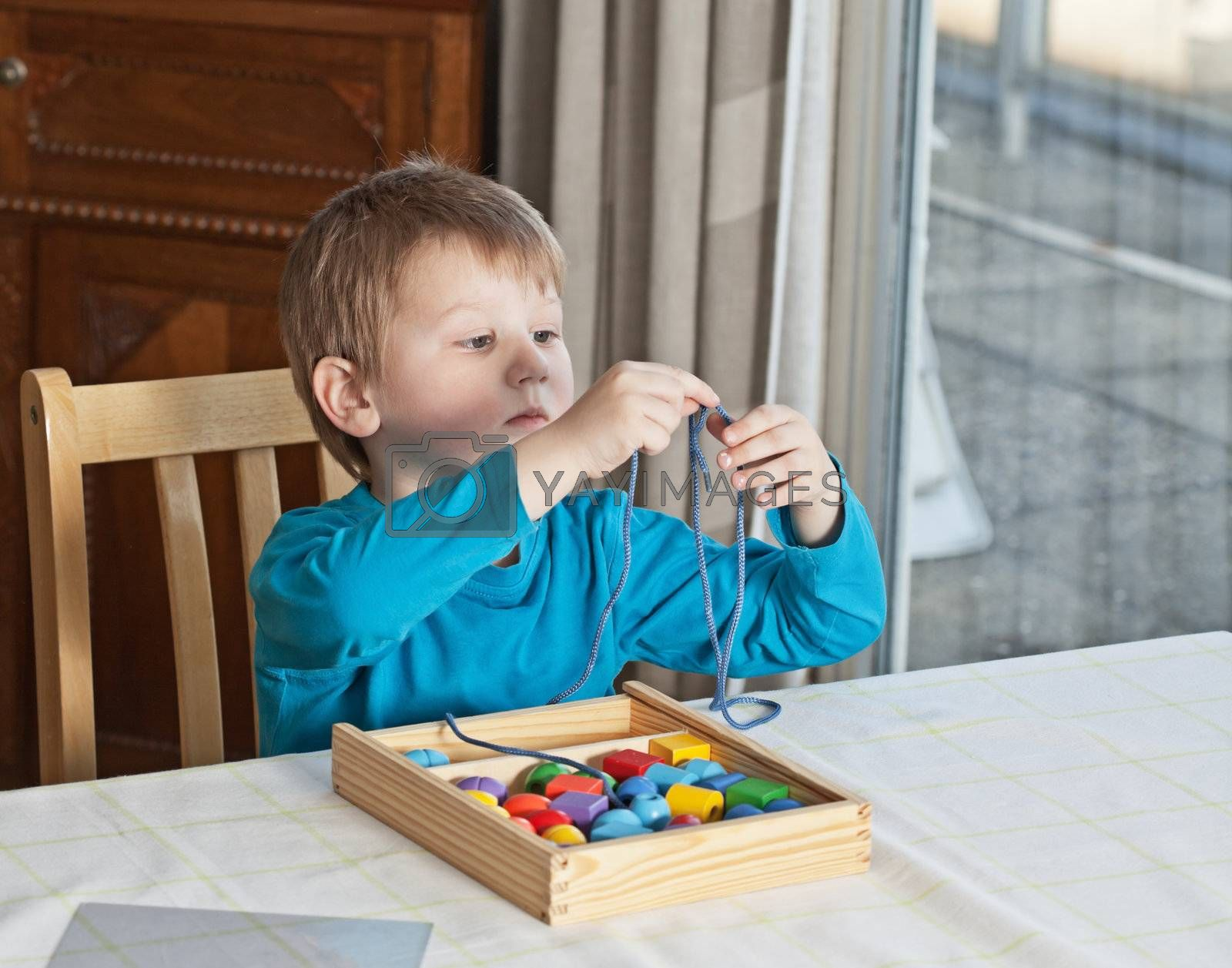 Little boy playing with colorful toys at home
