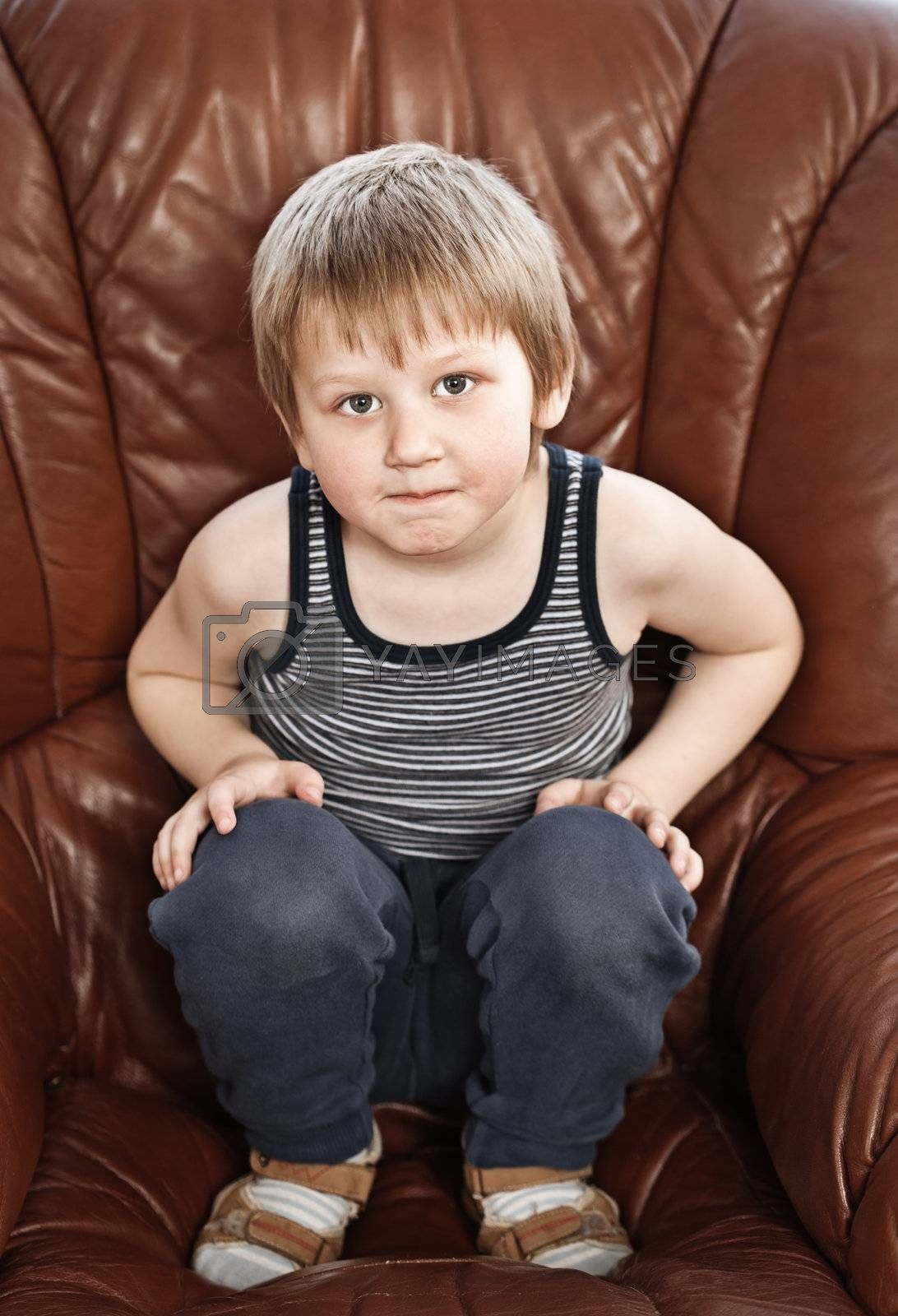 Portrait of cute blond little boy sitting in a leather armchair