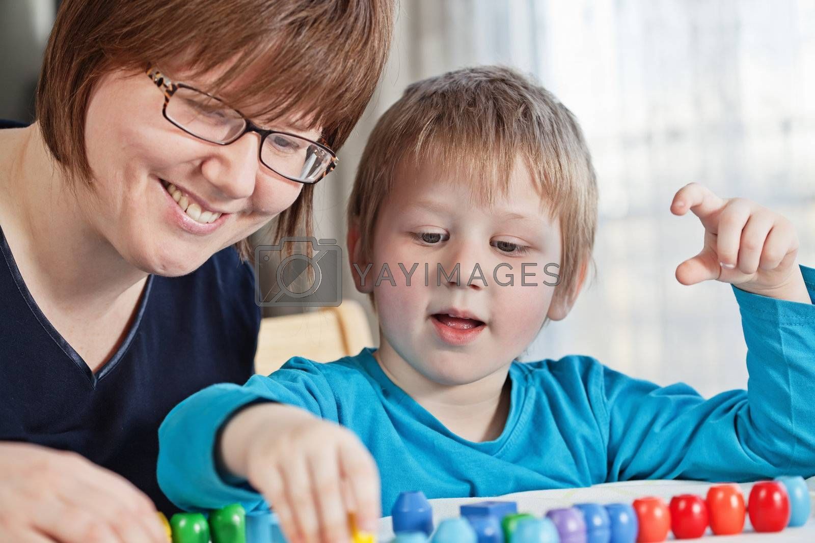Mother and her little son playing colorful toys at home