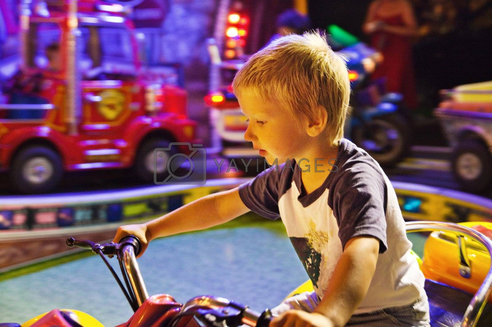 Little boy riding toy bicycle in amusement park