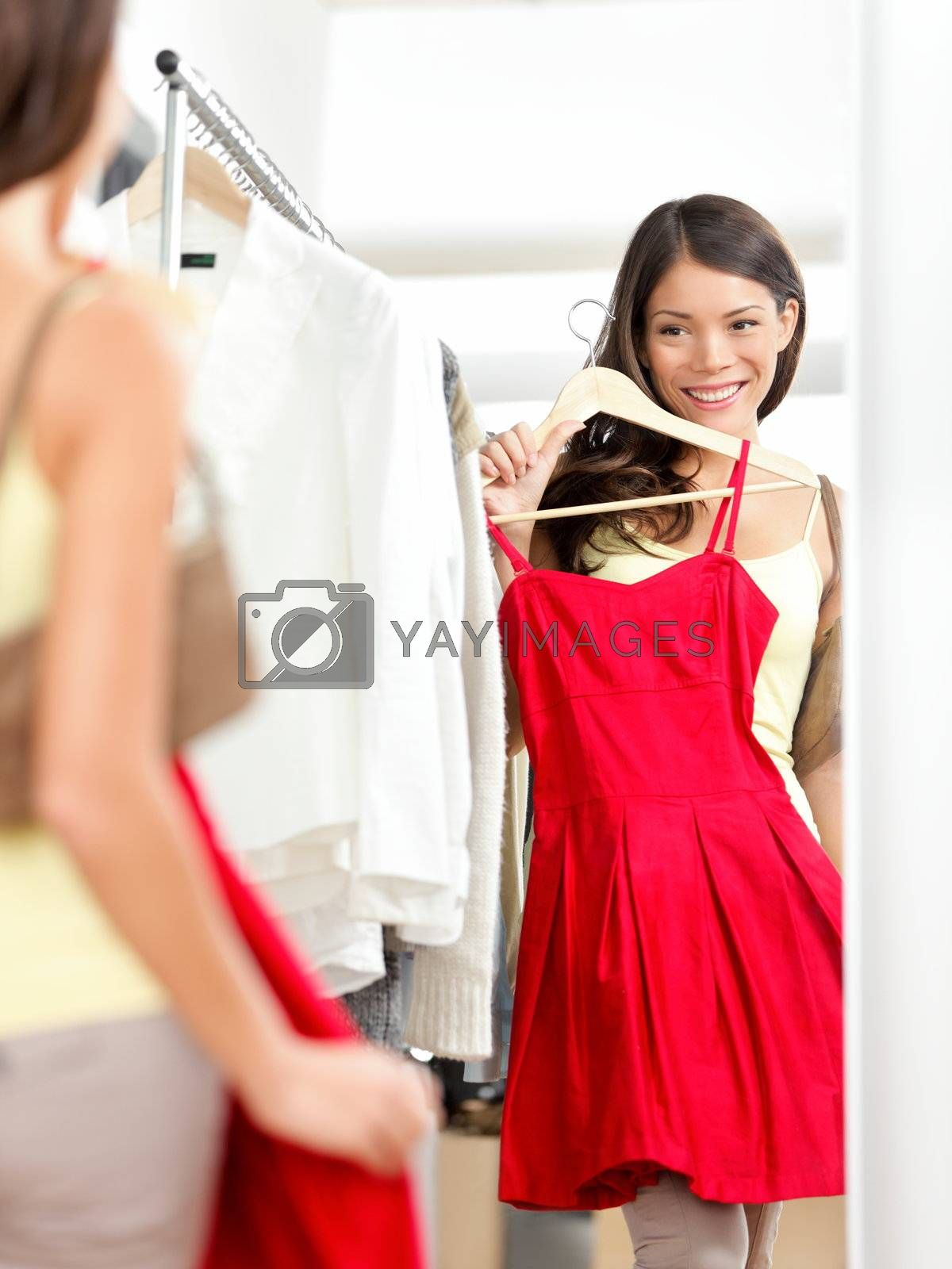 Shopper woman trying clothing dress while shopping in clothes store during sale. Beautiful young multicultural Asian / Caucasian female model smiling happy and joyful.