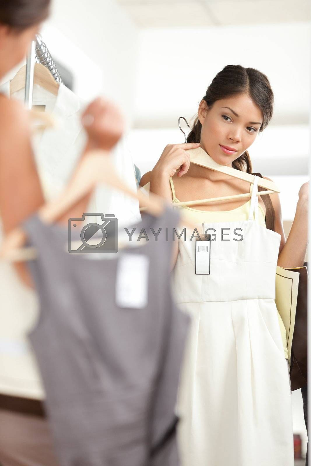 Woman shopping choosing dresses looking in mirror uncertain. Beautiful young multicultural shopper in clothing store.