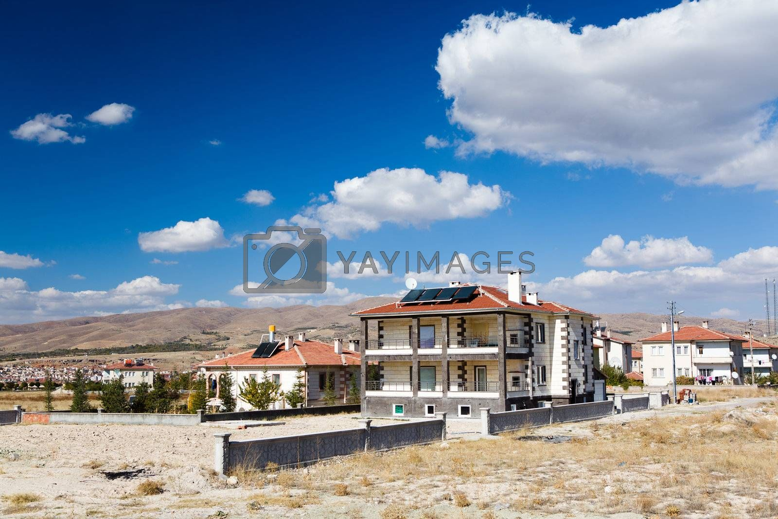 Houses with solar panels on red roofs under blue sky