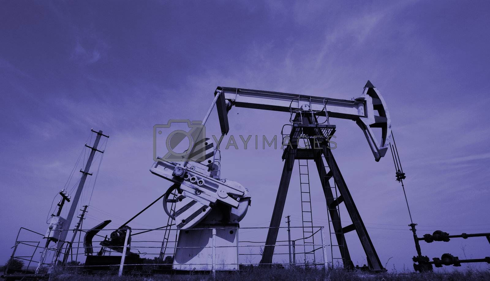 Extraction of oil. Pump jack and oil wellhead. Toned.