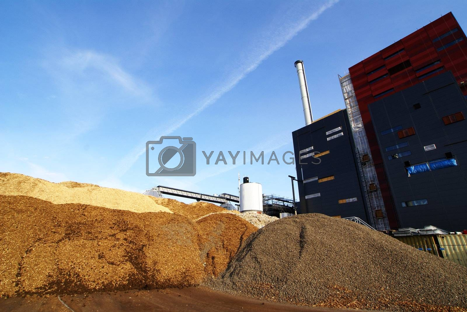 power plant with storage of wooden fuel against blue sky