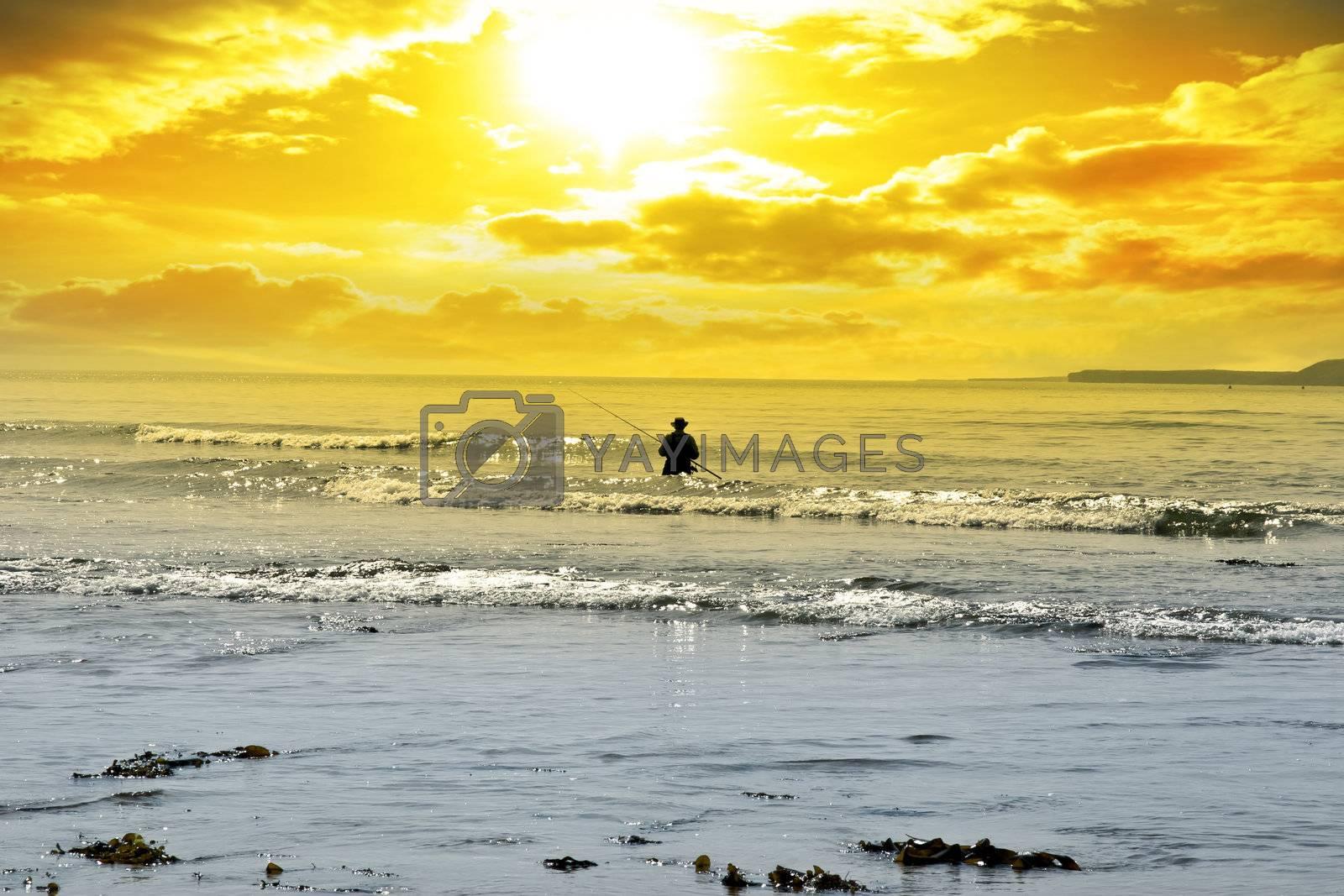 man fishing among the waves of the Atlantic ocean in Ballybunion county Kerry Ireland