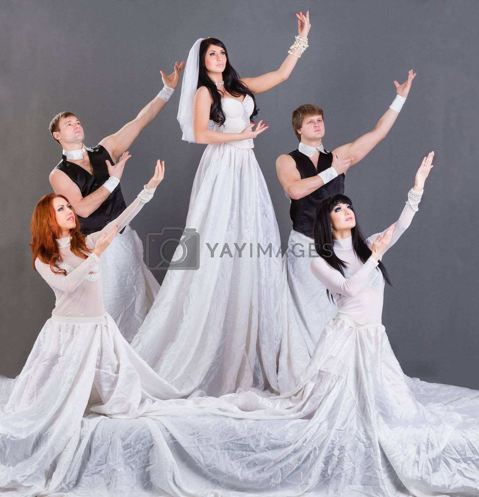 Actors in the wedding dress dancing. On a gray background in full length.