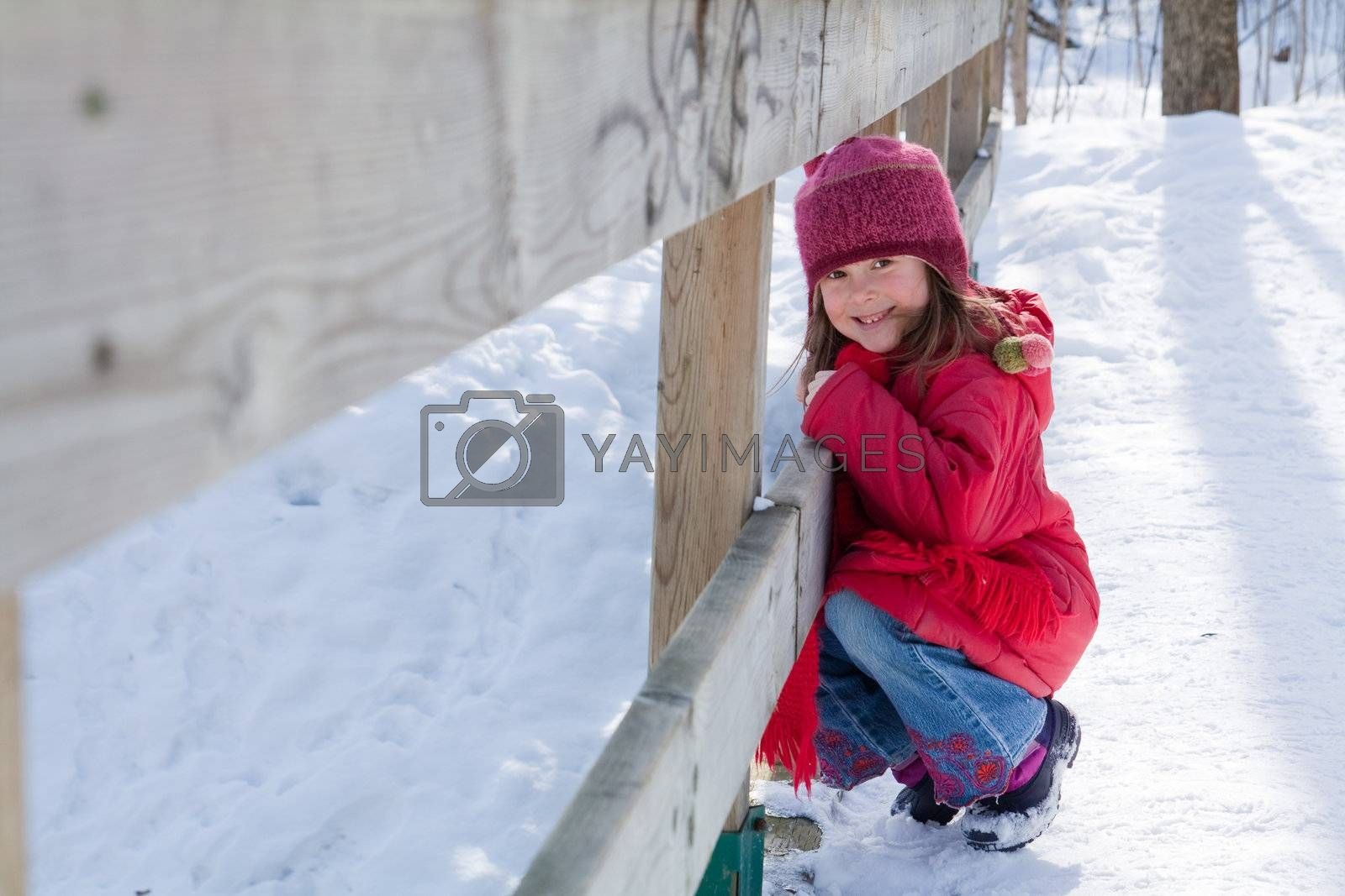 Cute little girl crouching by a fence on a wooden bridge