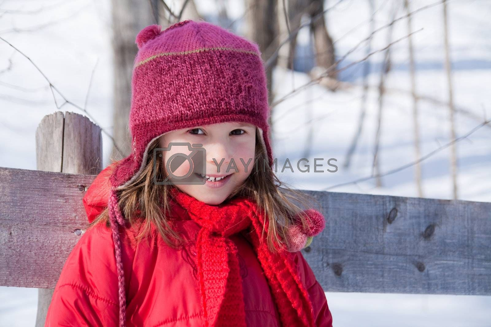 Cute little girl standing by a fence in winter