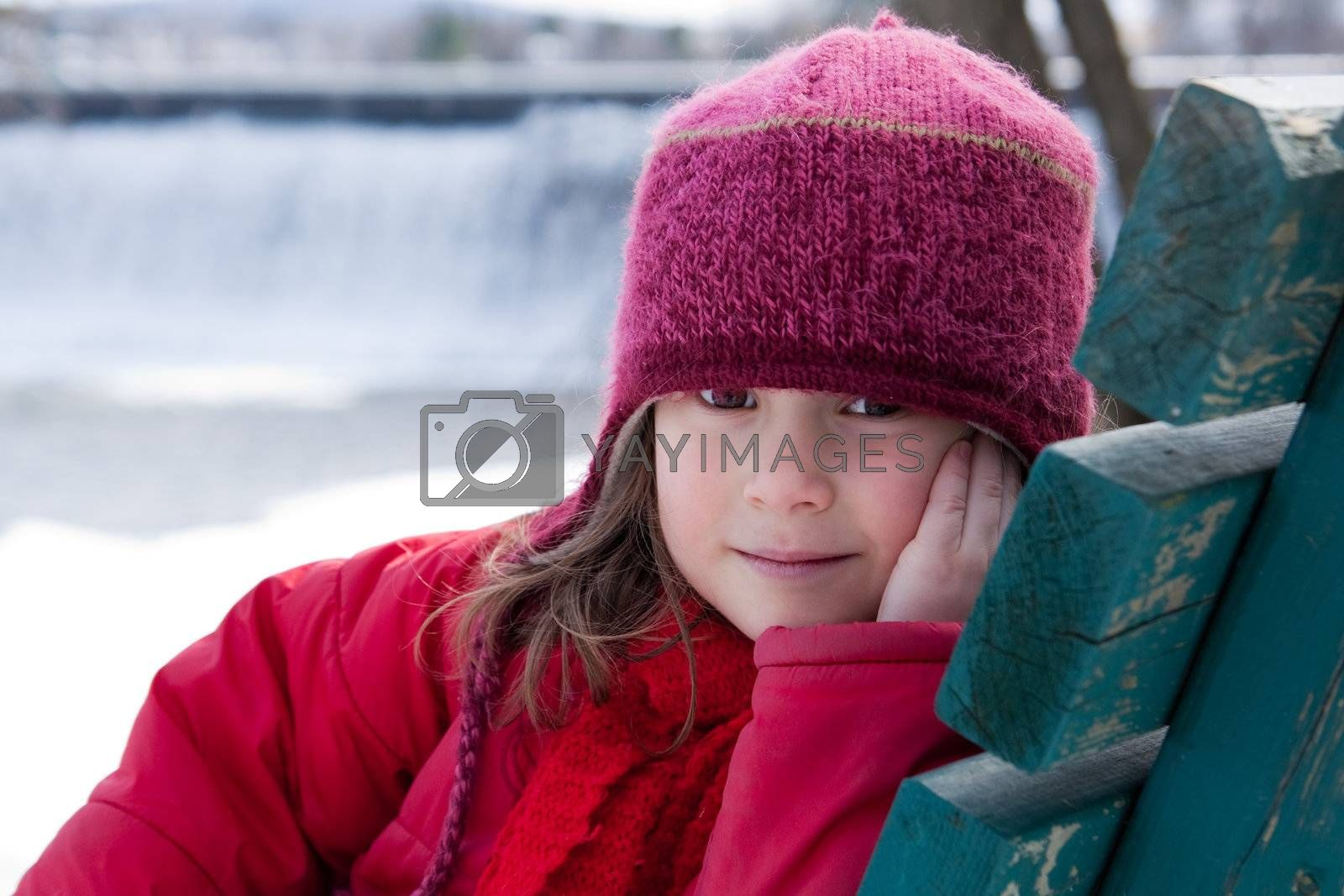 Cute little girl sitting on a bench in winter
