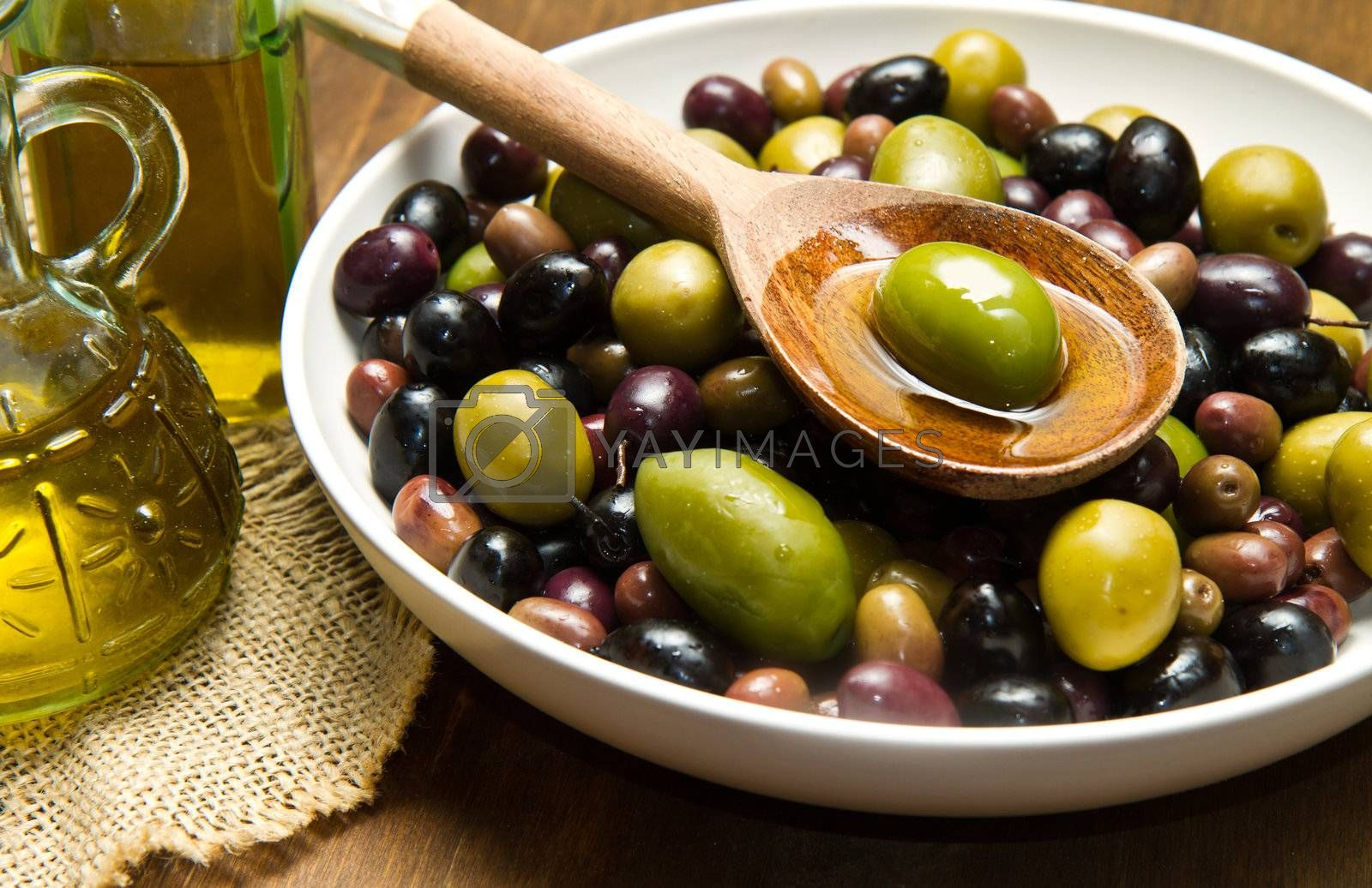 Extra virgin healthy Olive oil with fresh olives on rustic wooden background