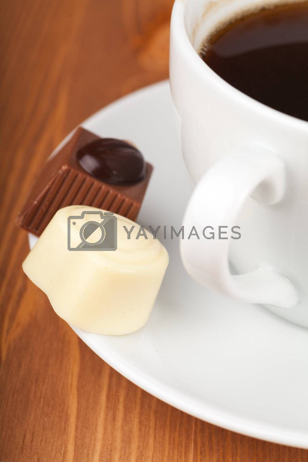Cup of coffee with chocolate candies on a wooden table