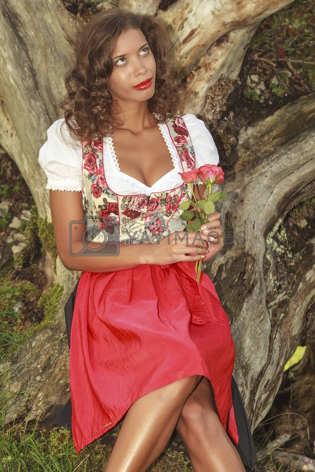 Brazilian woman in Bavarian dress with roses in hand dreams to himself.