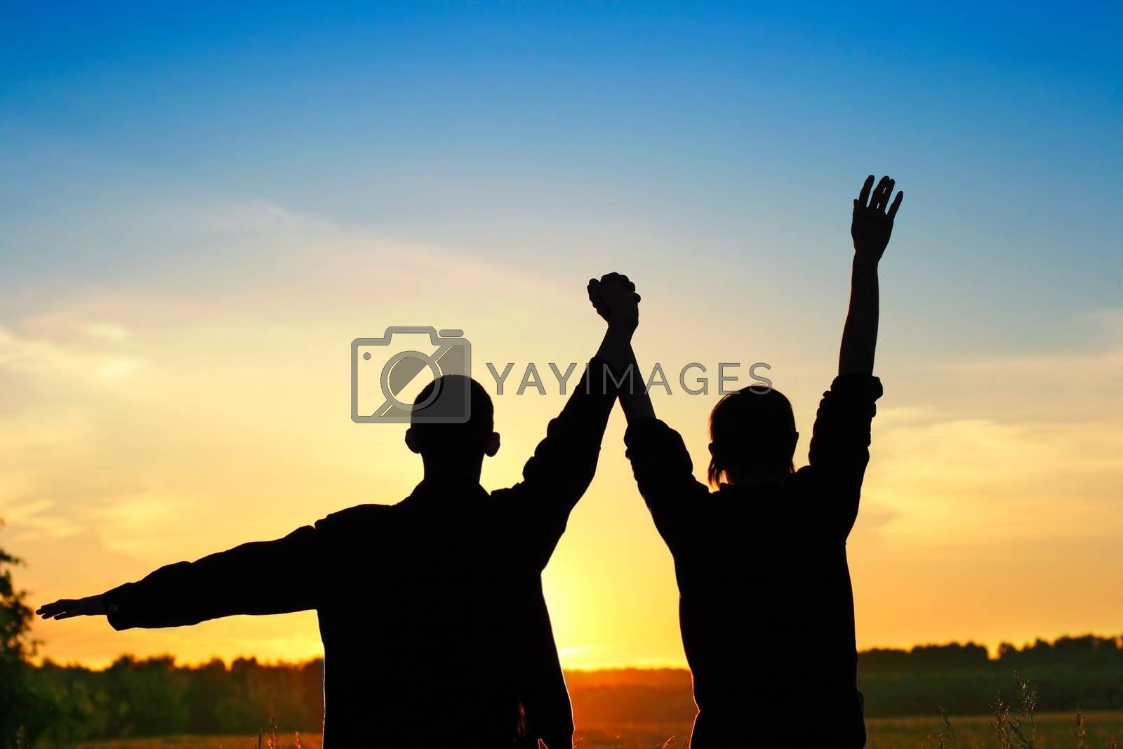 Silhouette of a Two Persons On Sunset In the Summer Field Background
