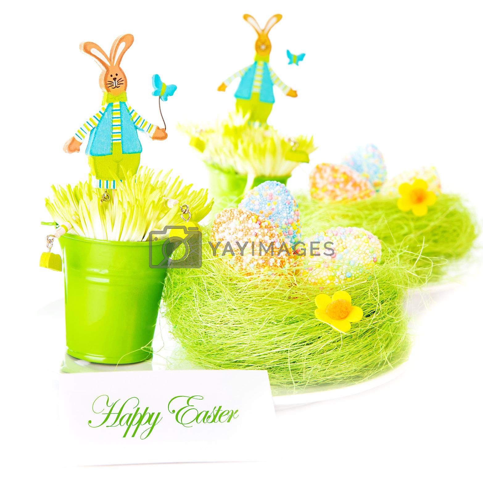 Beautiful colorful chicken eggs in the nest decorated with flowers and pretty rabbit toys isolated on white background, festive Easter postcard